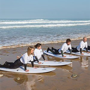 line of beginner surfers on boards during corporate team building lesson