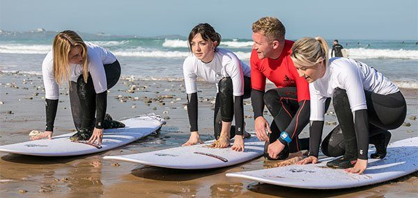 Beginner surfers learning basics on corporate team building surf lesson