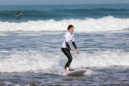 Girl learning to surf during beginner surf lessons