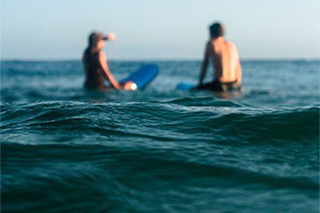 Couple sitting on surfboards during couples surf lesson
