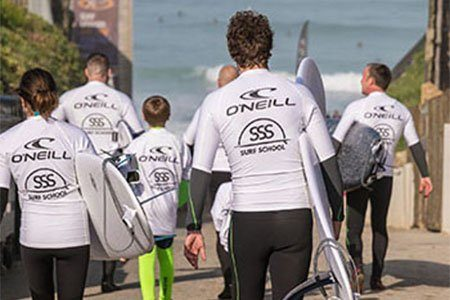 family carrying surfboards to beach on family surf lessons