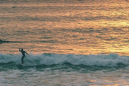 Surfer riding a wave during a sunset surf lesson
